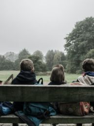 five children sitting on bench front of trees