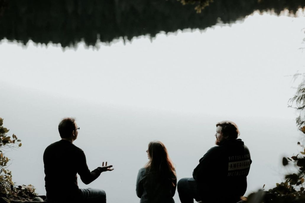 silhouette of three people sitting on cliff under foggy weather
